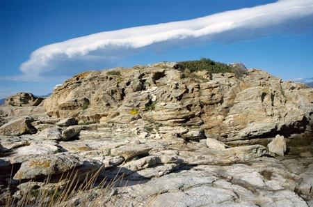 lenticular: Lenticular cloud in blue sky and rock in Corsica, France