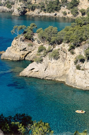 pine creek: Mediterranean shores with creeks on blue transparent water, and small boat near Bandol , in France