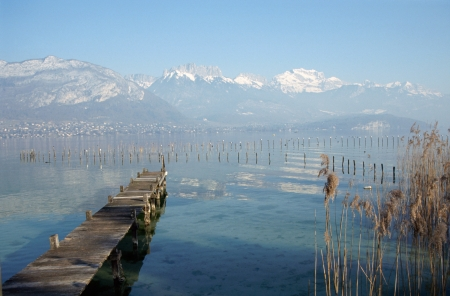 Wood pontoon, water, reeds bed and snowed mountains on Annecy lake, France Stock Photo - 13603739