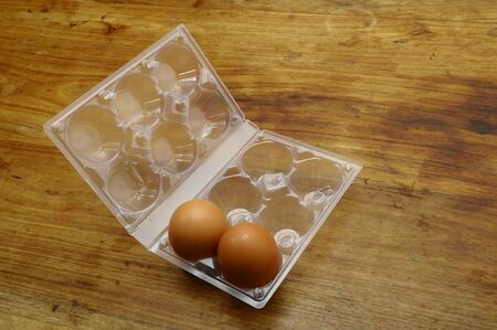 Eggs and plastic egg box on wooden farm table photo