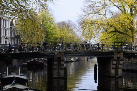 Bridge and bikes on canal in old city of Amsterdam, in Holland photo