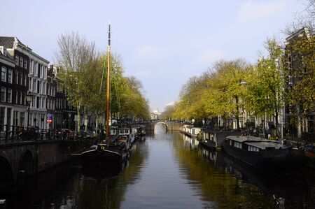 Boats on river and old city houses in Amsterdam - Holland photo
