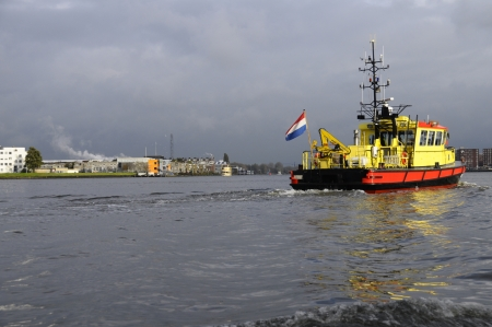 nederland: Red and yellow trawler with Nederland flag in Amsterdam harbor on a rainy day