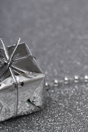 Silver gift box on gray brilliant background for merry christmas photo
