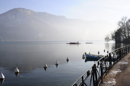 Dragon boat on  Annecy lake and mountains at morning on winter time, France Reklamní fotografie