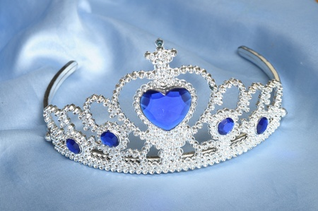 coquetry: Toy tiara with diamonds and blue gem, like a princess crown, on blue satin tissue