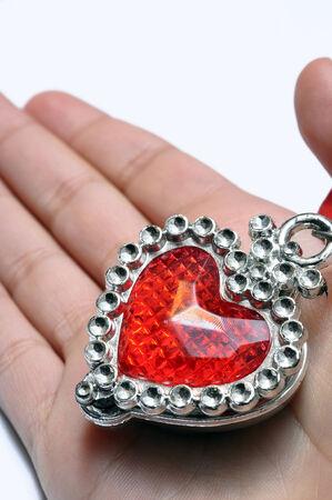 plastic heart: Red plastic heart in child hand on light background