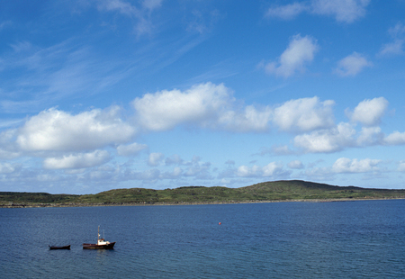connemara: Black Motor boat in Ireland, near Dingle, and blue sky with some clouds