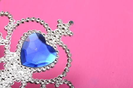 ピンクの背景にプリンセス クラウンのようなダイヤモンドと青の宝石とグッズ ティアラ 写真素材