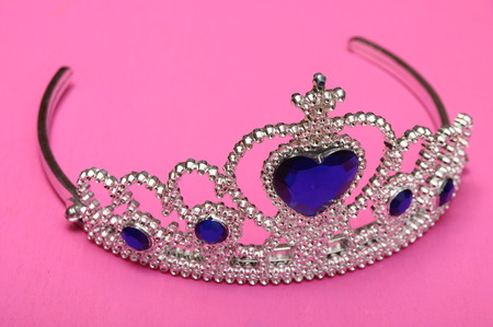 coquetry: Toy tiara with diamonds and blue gem, like a princess crown on pink background