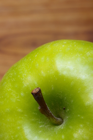 appetize: Macro of an appetizing  green granny smith apple over wooden background