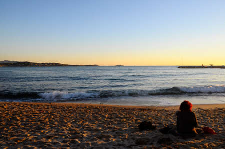 Red hair woman sitting on sand beach at sunset in Bandol, France photo