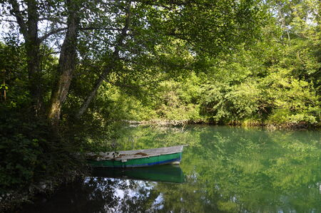 green river: Small green and blue fishing boat on green river of Aiguebelette in france Stock Photo