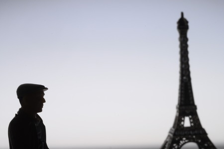 Old miniature man with a cap in front of Eiffel tower in France photo