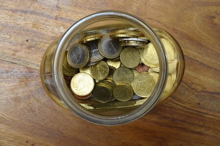 cents: Euro cents in a glass jar as wooden piggy bank on table