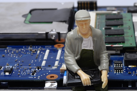 disassembly: Close up of Disassembled computer components and people  figurines