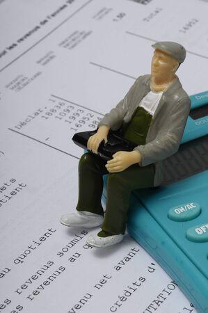 Schließen Sie oben von der Einkommensteuererklärung in Frankreich und in der Leutefigürchen, die auf Taschenrechner sitzt