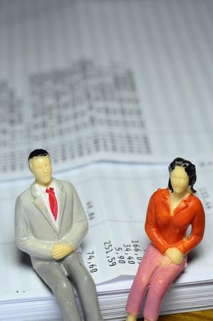 payroll: Miniature man and woman sitting on payroll Stock Photo