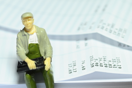 salaried: Miniture man with a cap sitting on payroll