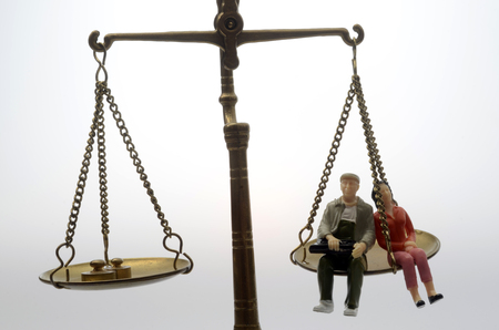disparity: Equality between man and women sitting on a weighing balance