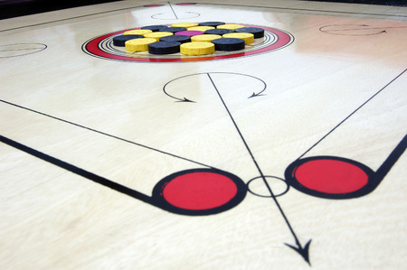 striker: Close up of Carrom board with striker and coins