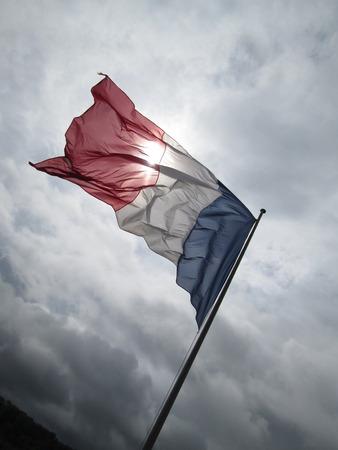 Mit Blick auf blowy Französisch Flagge und Sturm grauen Himmel