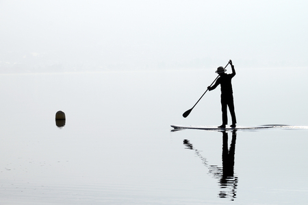 Paddle man rowing on quiet water of Annecy lake, France Stock Photo