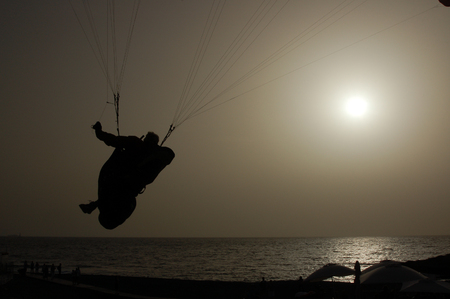 canaries: View of Paragliding backlit flying over a beach in Tenerife, Canaries Stock Photo