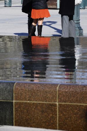 trouser legs: Men trouser legs and Woman legs qith orange skirt, in france Stock Photo