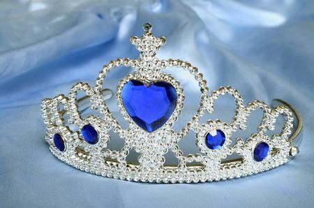 グッズ ティアラ ダイヤモンドやブルーの宝石、ブルーのサテン組織上のプリンセス クラウンのように