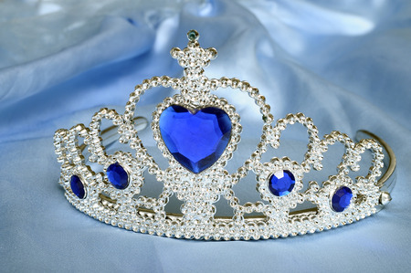 tiara: Toy tiara with diamonds and blue gem, like a princess crown, on blue satin tissue