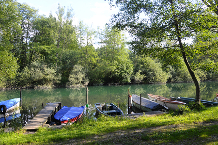 bucolic: Small green and blue fishing boat on green river of Aiguebelette in france Stock Photo