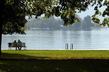 sitted: Couple sitted on bench, and Landscape of Annecy lake and mountains in Savoy, France
