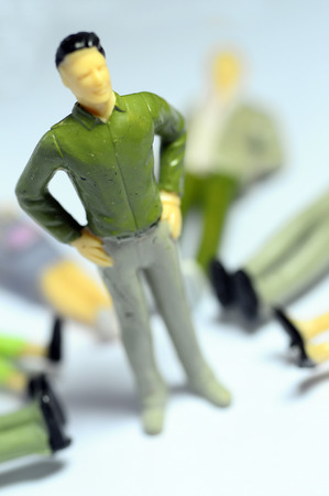 to dominate: Miniature man Man standing over lying figures on ground Stock Photo