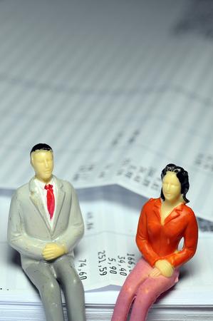 Miniature man and woman sitting on payroll Stock Photo