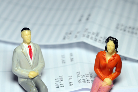 Miniature man and woman sitting on payroll Stock Photo