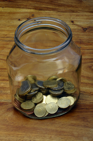 cents: Euro cents in a glass jar as piggy bank on wooden table
