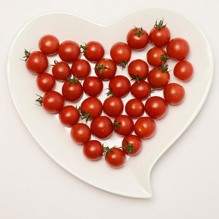 plato del buen comer: placa en forma de corazón y tomates rojos, el alimento sano Foto de archivo