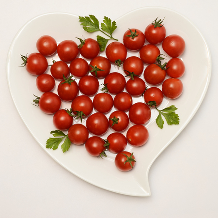 fond: Heart shaped plate and red tomatoes, healthy food