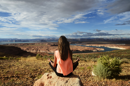 Young girl practising yoga in front of scenic view of lake powell, usa