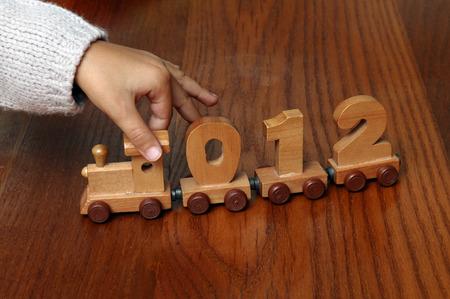Main de l'enfant jouant avec un train en bois, chiffres zéro, un, deux