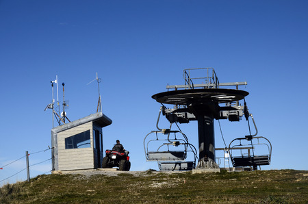 Ski lift in summer and man on quad in charge of maintenance, Semnoz, Savoy, France