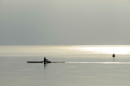 Rower man rowing on quiet water of annecy lake, Savoy, france