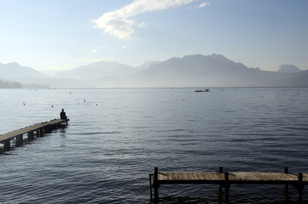 Man sitting on pontoon in front of lake annecy and mountains in savoy, france 版權商用圖片 - 92213324