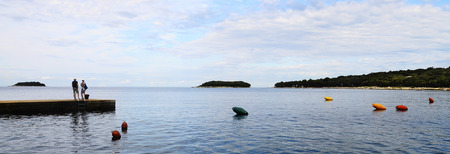 Man and woman couple looking at sea on pontoon, Croatia