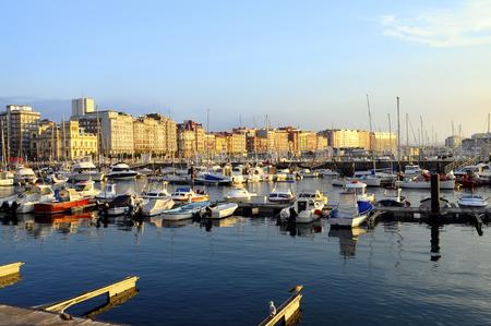 Toneel mening van Zonsondergang op stad Gijon en jachthaven in Noord-Spanje