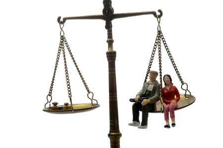 Equality between man and women sitting on a weighing balance