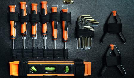 Opgeruimde gereedschapskist: schroevendraaier, niveaus, tangen op zwarte achtergrond