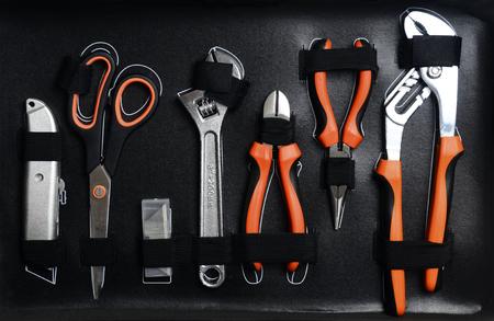 Opgeruimde gereedschapskist: mes, schaar, verstelbare sleutel, monseigneur clip op zwarte achtergrond