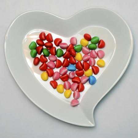 Heart shaped plate and lot of colored sweet candy